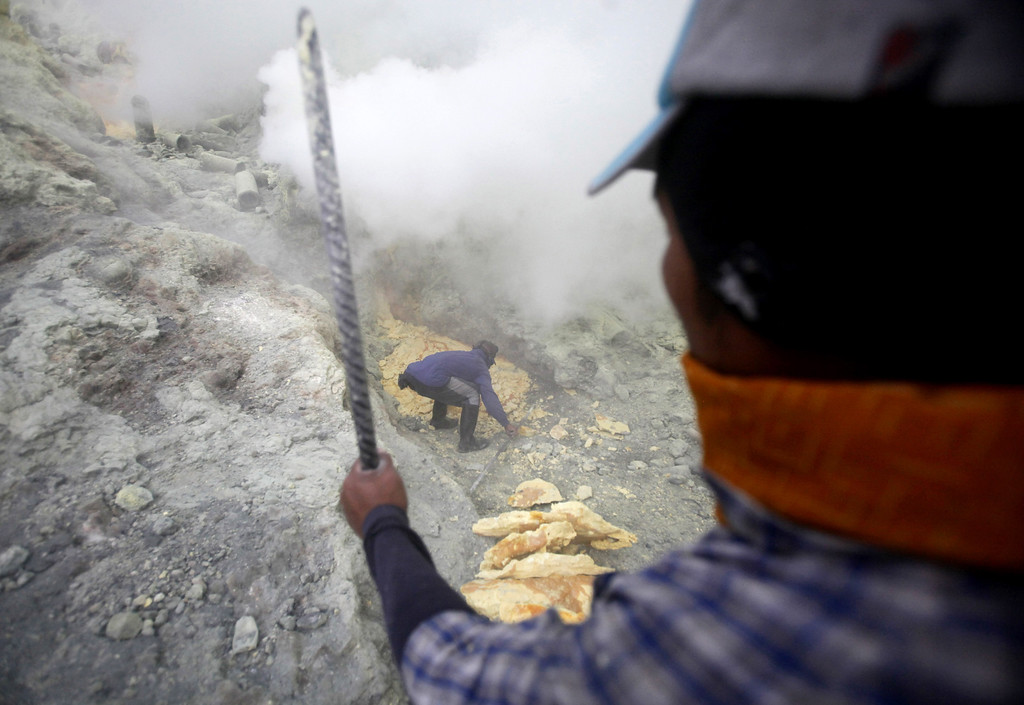 . In this April 16, 2016 photo, miners dig out sulfur rocks at the crater of Mount Ijen in Banyuwangi, East Java, Indonesia.  (AP Photo/Binsar Bakkara)