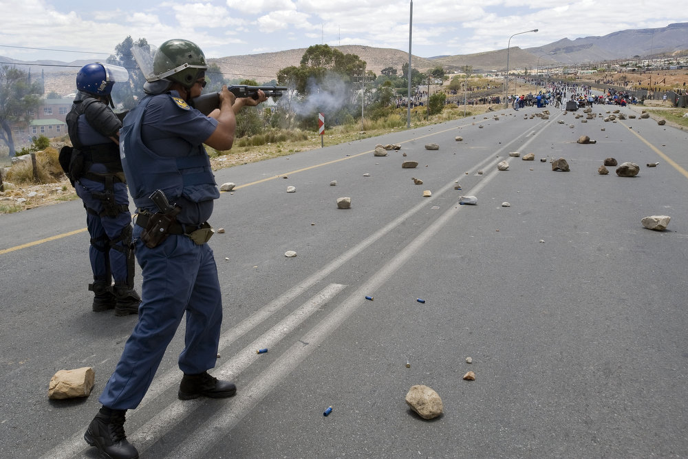 Description of . Members of the South African Police Services fire rubber bullets at striking farmworkers during violent clashes, on January 10, 2012 in De Doorns, a small farming town about 140Km North of Cape Town, South Africa. The farm workers have said that they they will not return to work on the fruit growing region's farms until they receive a daily wage of at least R150($17) per day, which is about double what they currently earn. One of the men wears a red t-shirt of the ruling African National Congress(ANC).  AFP PHOTO / RODGER  BOSCH/AFP/Getty Images