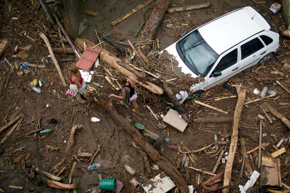 Description of . Residents walk through debris left by a flood caused by heavy rains in the Xerem neighborhood, about 31 miles north of Rio de Janeiro, Brazil, Thursday, Jan. 3, 2013. Nearly 8.5 inches of rain fell in just 24 hours in the mountainous region north of Rio. Hard rains in Brazil are creating a state of alert in Rio de Janeiro and in nearby spots where flood-triggered mudslides have killed hundreds in recent years.  (AP Photo/Felipe Dana)