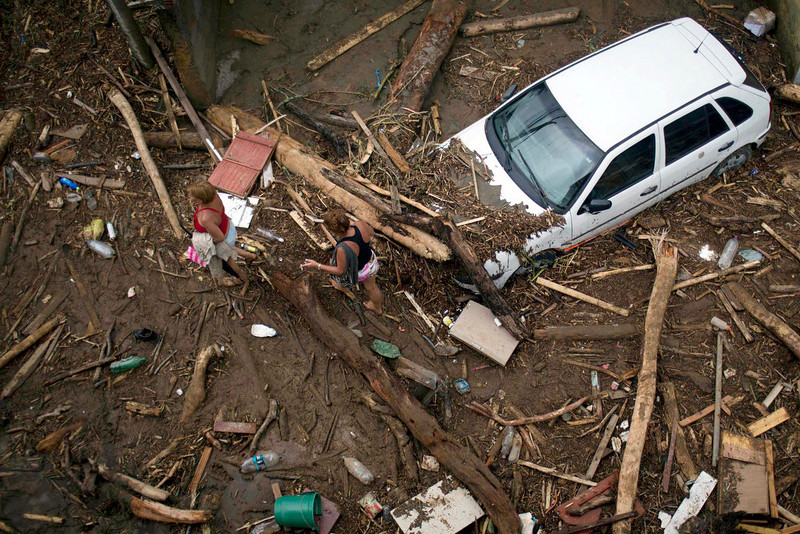 . Residents walk through debris left by a flood caused by heavy rains in the Xerem neighborhood, about 31 miles north of Rio de Janeiro, Brazil, Thursday, Jan. 3, 2013. Nearly 8.5 inches of rain fell in just 24 hours in the mountainous region north of Rio. Hard rains in Brazil are creating a state of alert in Rio de Janeiro and in nearby spots where flood-triggered mudslides have killed hundreds in recent years.  (AP Photo/Felipe Dana)