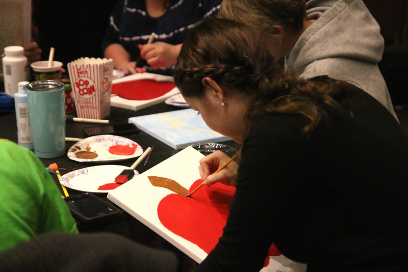 A student painting an apple on her canvas provided by Student Activities.
