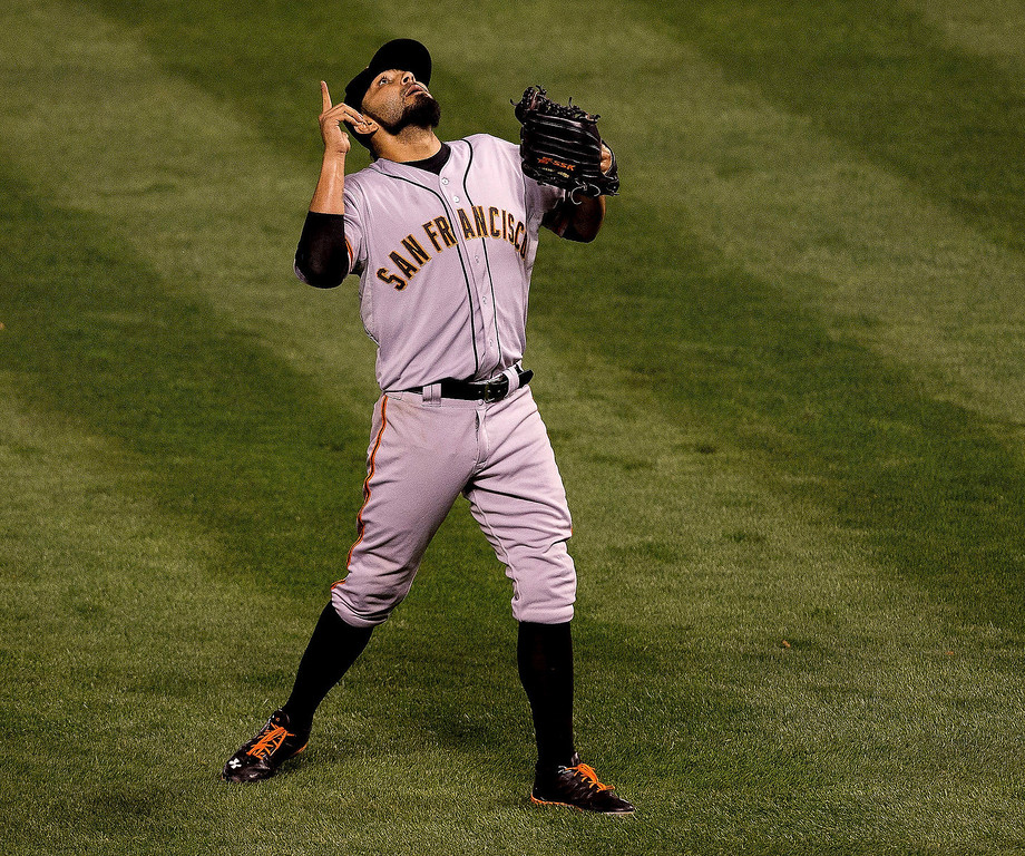 . Sergio Romo #54 of the San Francisco Giants points to the sky to celebrate after he helped the Giants defeat the Colorado Rockies 5-3 at Coors Field on August 27, 2013 in Denver, Colorado.  (Photo by Justin Edmonds/Getty Images)