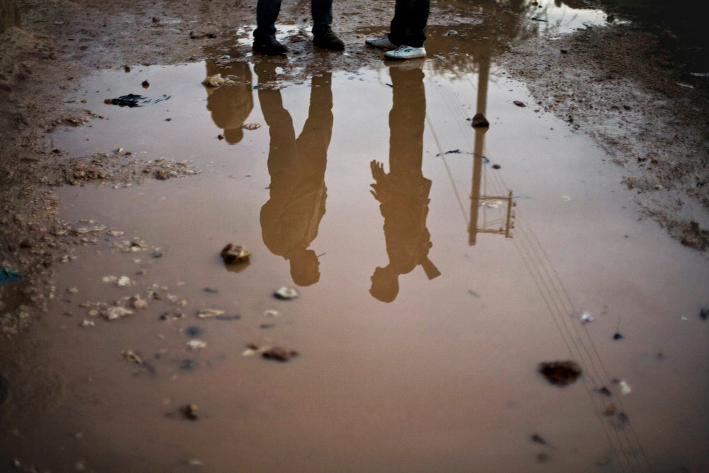 Description of . In this Wednesday, Dec. 12, 2012 photo, Free Syrian Army fighters are seen reflected in running water in the northern province of Aleppo, Syria. Syria's civil war has killed more than 40,000 people. (AP Photo/Manu Brabo)