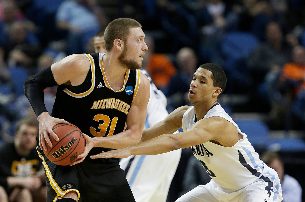 . Milwaukee\'s Matt Tiby (31) protects the ball from Villanova\'s Josh Hart during the second half of a second-round game in the NCAA college basketball tournament in Buffalo, N.Y., Thursday, March 20, 2014. (AP Photo/Frank Franklin II)