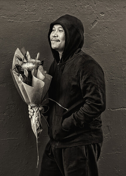 I approached this individual in West Seattle and asked to take his portrait. He gladly allowed me to do so, but as I started to take shots he began laughing and smiling. I turned to see a woman in a pink outfit approach us from the side. She would soon receive the bouquet.