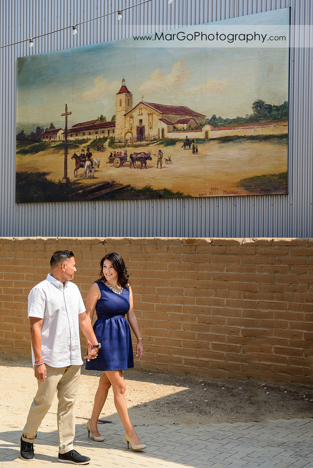 woman in blue dress and man in white shirt holding hands and walking in the patio of San Jose San Pedro Square Market during engagement session