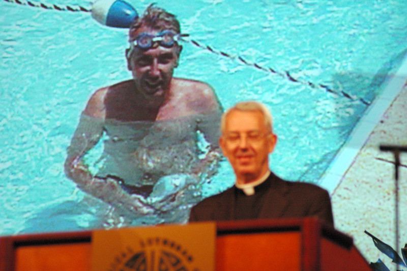 """We are one church,"" Secretary Almen reminded. With a video clip from his 1991 report behind him, Almen related again how, just as with swimming, many parts do make one cohesive whole."
