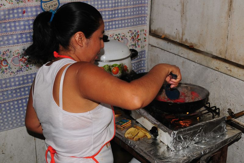 This woman, a recipient of an Amextra microfinance loan, works hard to prepare foods for her customers in the town of Playa Catazaja.