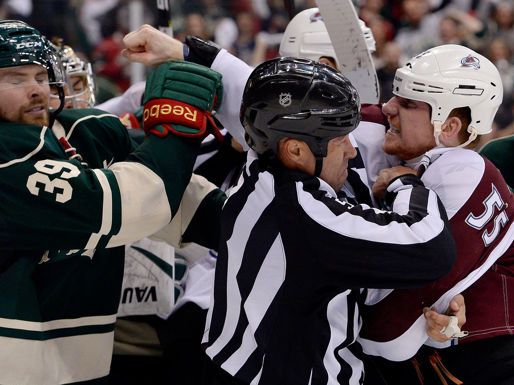 . Colorado Avalanche left wing Cody McLeod (55) tries to land a punch on Minnesota Wild defenseman Nate Prosser (39) as linesman Jay Sharrers (57) tries to break them up at the end of the game April 28, 2014 in Game 6 of the Stanley Cup Playoffs at Xcel Energy Center. Minnesota Wild defeated the Colorado Avalanche 5-2 to force a game 7 in Denver.  (Photo by John Leyba/The Denver Post)