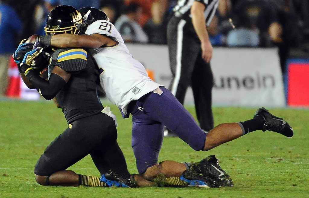 . UCLA Bruins wide receiver Devin Fuller (7) catches a pas for a first down as Washington Huskies defensive back Marcus Peters (21) makes the tackle during the first half of their college football game in the Rose Bowl in Pasadena, Calif., on Friday, Nov. 15, 2013.  UCLA won 41-31.   (Keith Birmingham Pasadena Star-News)