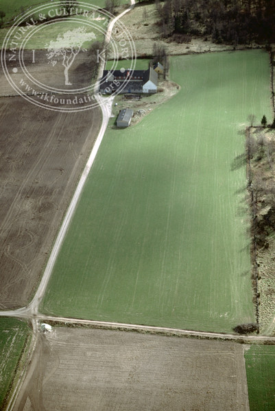 Farmland west of Ravlunda church - with plantations, buildings and prehistoric remains (2 April, 1989). | LH.0525