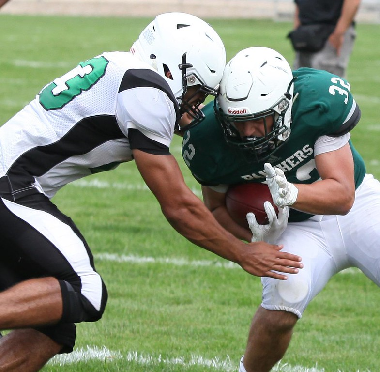 . Randy Meyers - The Morning Journal Leighton Banjoff of Elyria Catholic is met by Columbia\'s Brandon Coleman after a short gain during a scrimmage.