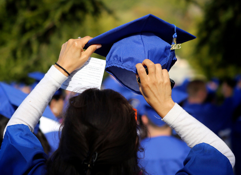 . A graduate adjusts her cap while she waits to graduate from Cabrillo College on Friday. (Kevin Johnson/Sentinel)