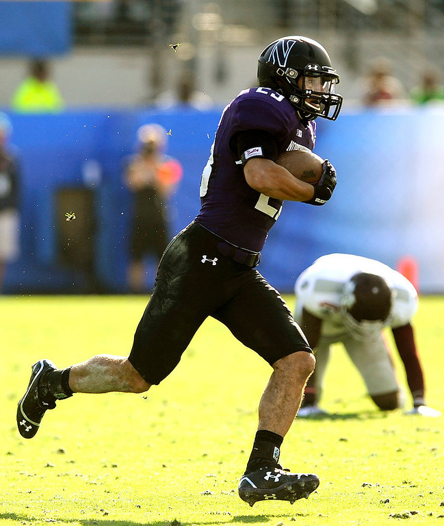. Northwestern defensive back Nick VanHoose (23) runs back a interception during the second half of the Gator Bowl NCAA college football game against Mississippi State, Tuesday, Jan. 1, 2013 in Jacksonville, Fla. Northwestern beat Mississippi State 34-20.  (AP Photo/Stephen Morton)
