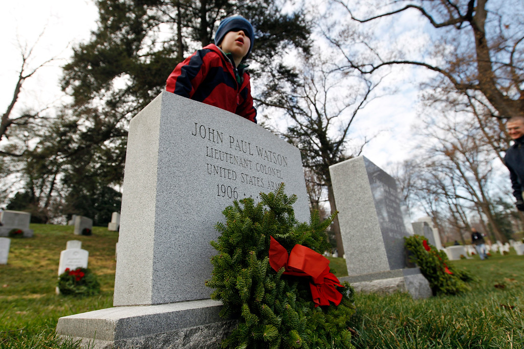 . Volunteer Tyler J. Benson 4,  helps his family to lay holiday wreaths at graves at Arlington National Cemetery in Arlington, Va., Saturday Dec. 15, 2012, during Wreaths Across America Day. Wreaths Across America was started in 1992 at Arlington National Cemetery by Maine businessman Morrill Worcester and has expanded to hundreds of veterans\' cemeteries and other locations in all 50 states and beyond.  (AP Photo/Jose Luis Magana)