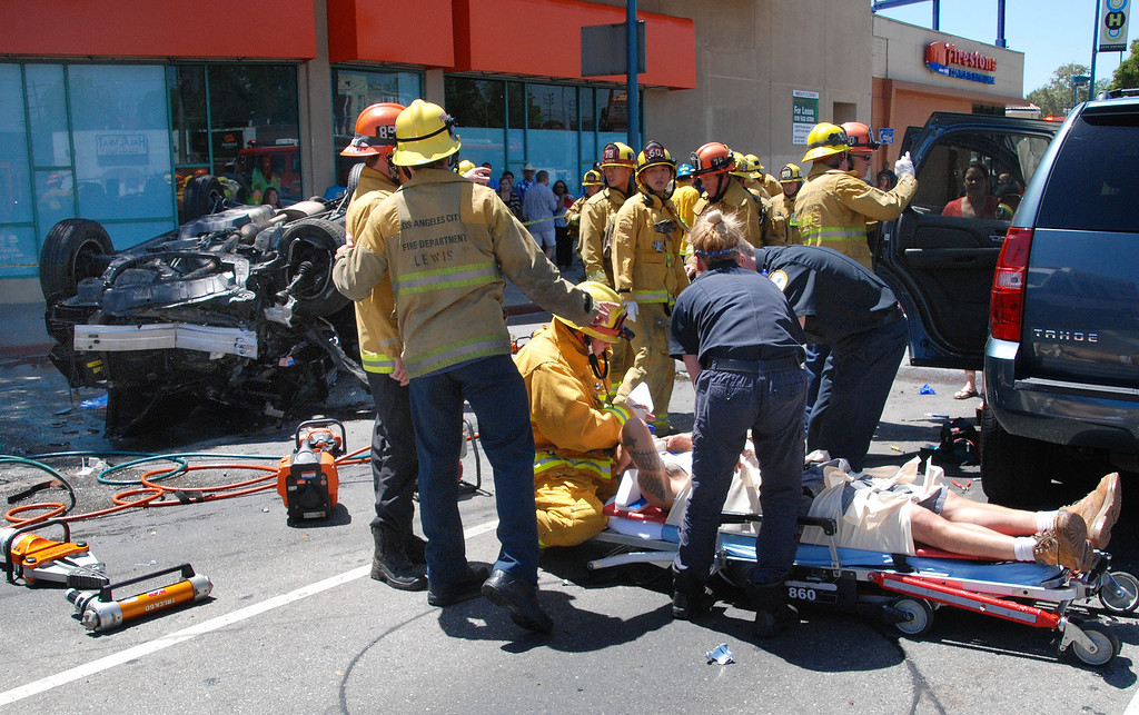 . North Hollywood, Ca. LAFD firefighters treat one of 4 victims involved in a grinding three car accident that left one dead at Lankershim Bl and Vineland Av in North Hollywood. Two males and two females were transported to various hospitals with injureis that ranged from moderate to serious.