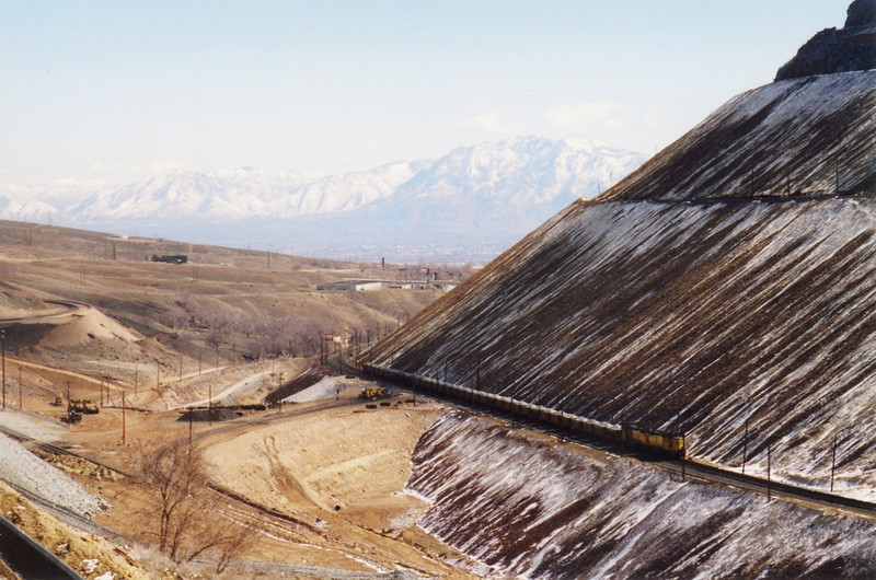 The last ore train from Bingham Canyon, on the right, passes the new Dry Fork reload site, on the left. Note the new crossover track and fill that allows access from the lower transportation line (where the ore train is), over to the reload track. March 19, 2000.