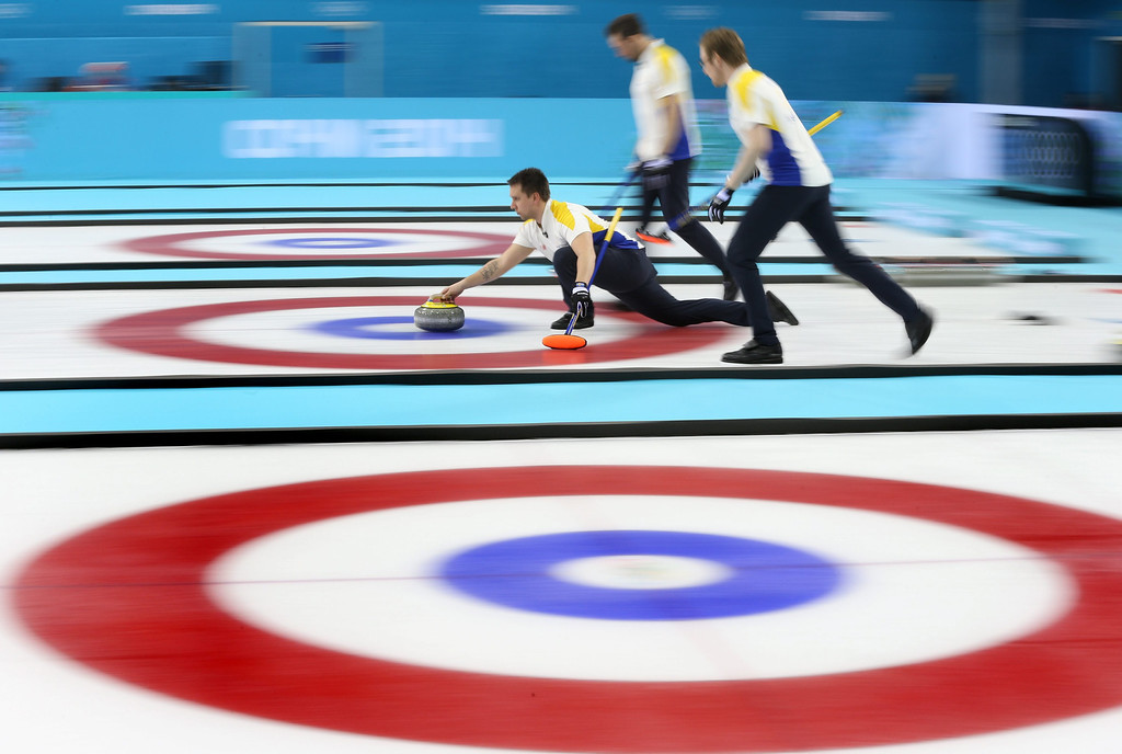 . Fredrik Lindberg (L) of Sweden delivers a stone during the bronze medal match between Sweden and China in the men\'s Curling competition in the Ice Cube Curling Center at the Sochi 2014 Olympic Games, Sochi, Russia, 21 February 2014.  EPA/TATYANA ZENKOVICH