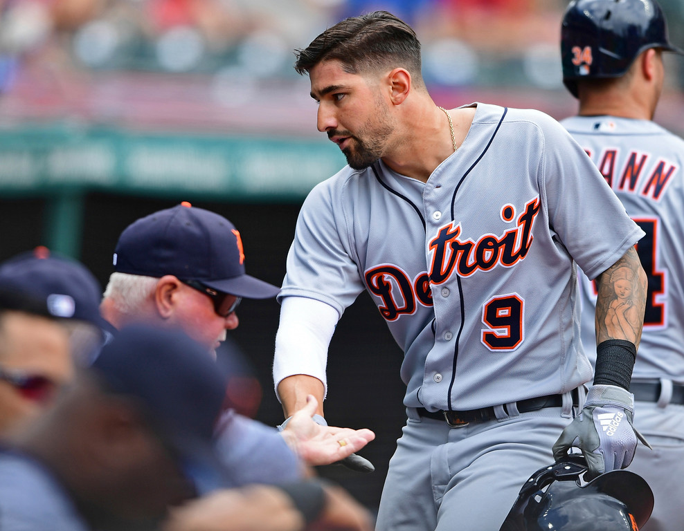 . Detroit Tigers\' Nicholas Castellanos is congratulated in the dugout after scoring a run in the fourth inning of a baseball game against the Cleveland Indians, Sunday, June 24, 2018, in Cleveland. (AP Photo/David Dermer)