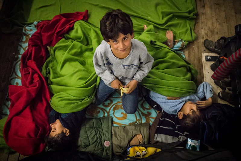 In a refugee camp in Berlin, the elder brother takes care of his younger siblings while they sleep on the floor. Berlin, Germany. November 2015. ----------- Le frère ainé veille sur ses deux jeunes frères assoupis sur le plancher d'un camp de réfugiés à Berlin. Berlin, Allemagne. Novembre 2015.