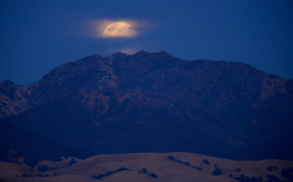 . The supermoon rises behind cloud cover above the summit of Mount Diablo as seen from Dinosaur Hill Park in Pleasant Hill, Calif., on Sunday, Aug. 10, 2014. (Jose Carlos Fajardo/Bay Area News Group)