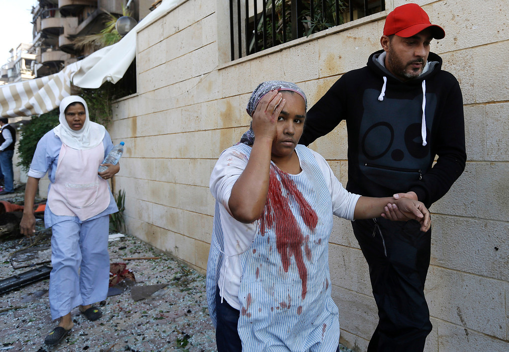 . A Lebanese man helps an injured domestic worker, at the scene where two explosions have struck near the Iranian Embassy killing many, in Beirut, Lebanon, Tuesday Nov. 19, 2013. The blasts in south Beirut\'s neighborhood of Janah also caused extensive damage on the nearby buildings and the Iranian mission. The area is a stronghold of the militant Hezbollah group, which is a main ally of Syrian President Bashar Assad in the civil war next door. It\'s not clear if the blasts are related to Syria\'s civil war. (AP Photo/Hussein Malla)