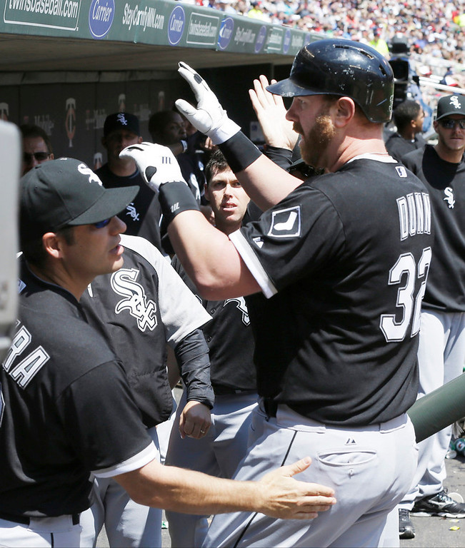 . Chicago\'s Adam Dunn is welcomed in the dugout after hitting a two-run home run off Minnesota Twins pitcher Mike Pelfrey in the third inning. (AP Photo/Jim Mone)