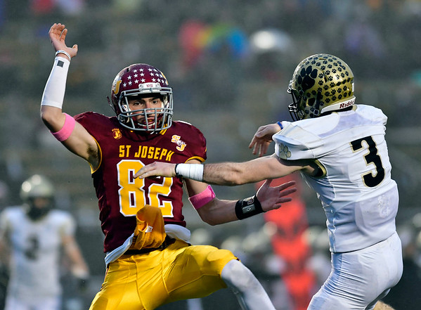 12/14/2019 Mike Orazzi | Staff St. Joseph High School's William Diamantis (82) and Daniel Hand's Isaiah McNeilly (3) during a 17-13 Cadets win at Veteran's Stadium in New Britain on Saturday.  .