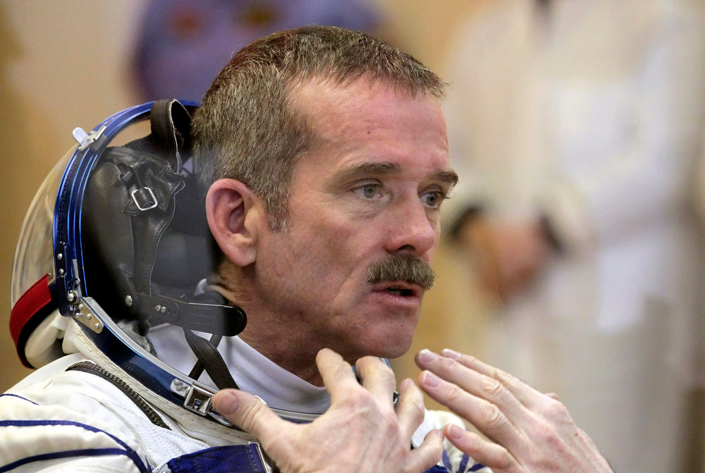 Description of . Member of the next expedition to the International Space Station, Canadian astronaut Chris Hadfield speaks during the pre-launch preparations at the Baikonur cosmodrome in Kazakhstan, Wednesday, Dec. 19, 2012.  (AP Photo/Maxim Shipenkov, Pool)