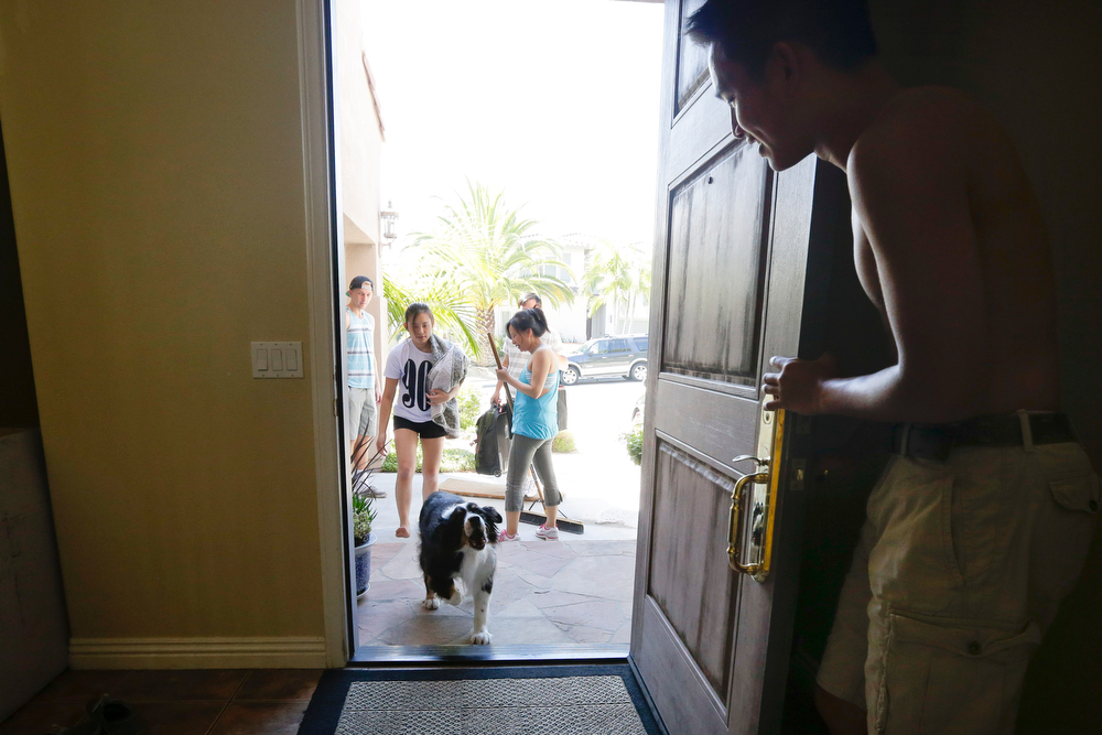 . Sean Teng, right, holds open the front door as the Teng family dog Pup arrives home from wildfire evacuations, Friday, May 16, 2014, in Carlsbad, Calif. Behind, Snow, Teng sweeps while Annie and Logan Teng walk inside. Some evacuation orders were lifted early Friday in an area near the fiercest of several wildfires in San Diego County, as crews building containment lines around the blazes hoped cooler temperatures will help them make further progress. (AP Photo/Gregory Bull)