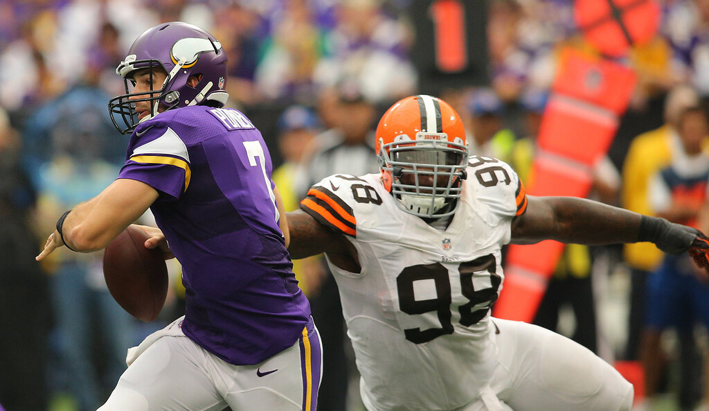 . Christian Ponder #7 of the Minnesota Vikings scrambles away from Phillip Taylor #98 of the Cleveland Browns on September 22, 2013 at Mall of America Field at the Hubert Humphrey Metrodome in Minneapolis, Minnesota. (Photo by Adam Bettcher/Getty Images)