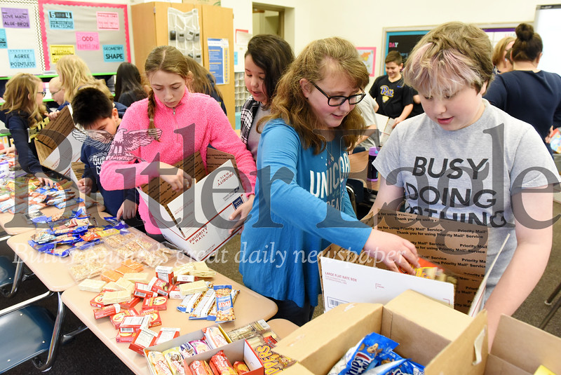 Harold Aughton/Butler Eagle: Sixth Graders from Mrs. Hovanick's class prepare care packages for soldiers stationed abroad.