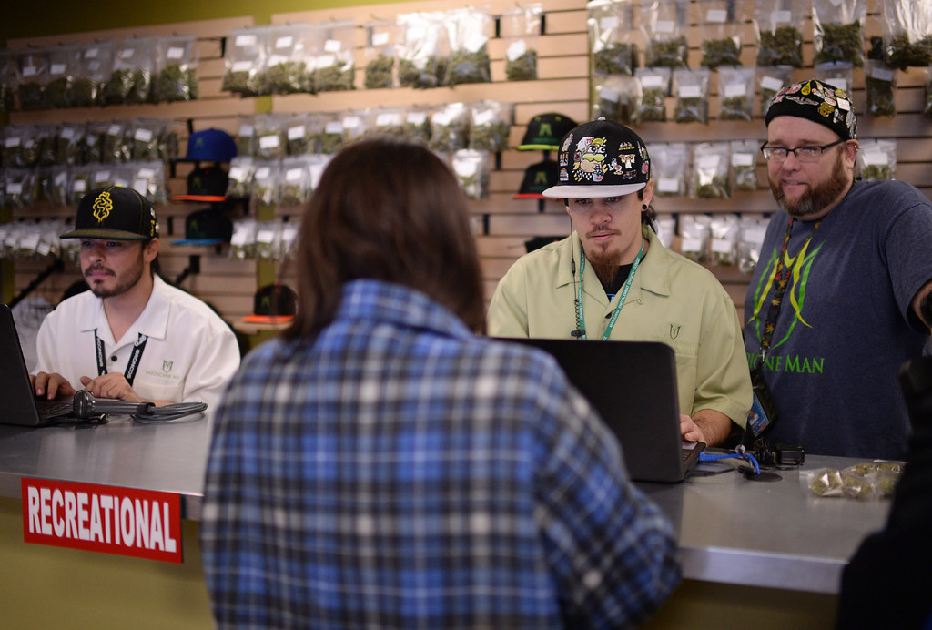 . DENVER, CO. JANUARY 01: From left behind the counter, David Marlow, Ryan Luck and Jason Coleman, staff members at Medicine Man marijuana dispensary, take care of customers on New Years day morning in Denver, Colorado January 1, 2014. (Photo by Hyoung Chang/The Denver Post)