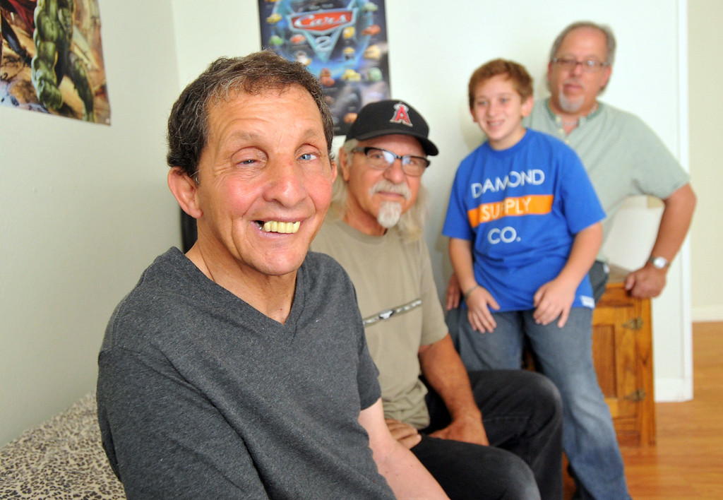 . Gary Borack, 58, left, is joined by his brothers, Robert, center, and John and nephew, Michael, 11, at his group home in Mission Viejo on Wednesday June 26, 2013. Gary Borack, who was diagnosed with severe mental retardation at the age of 5, recently transitioned out of Lanterman Developmental Center in Pomona about 9 months ago, and is living successfully in the group home. (SGVN/Staff Photo by Keith Durflinger)