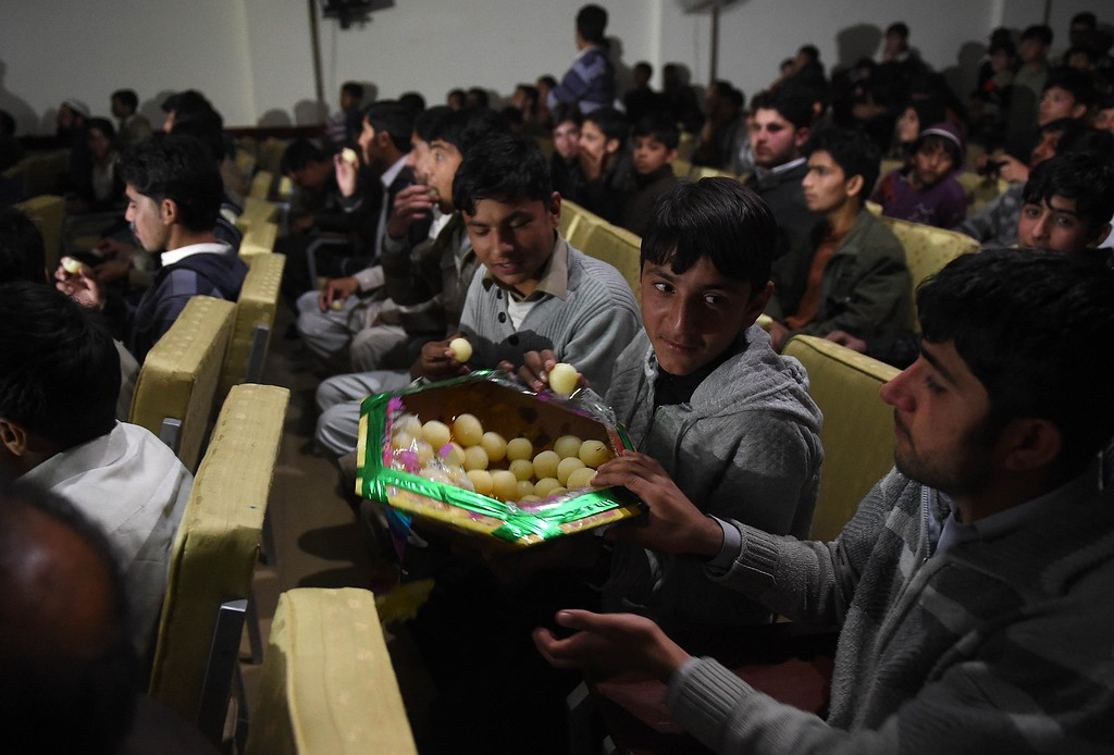 . Pakistan residents disribute sweets as they watch a live broadcast of the award ceremony of joint Nobel Peace Prize laureate, Malala Yousafzai at a school hall in her home town of Mingora, a district of Swat valley on December 10, 2014.  Hundreds of residents in Malala Yousfazai\'s hometown cheered as they watched their hero accept her Nobel Peace Prize on a giant TV, as Pakistan\'s Prime Minister promised the activist\'s dream for girls\' education would come true. AFP PHOTO /A MAJEEDA Majeed/AFP/Getty Images