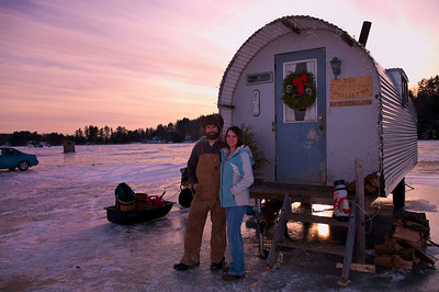 Kevin and Tanya Ouellette in front of their ice shack at sunset, Sabattus, Maine.
