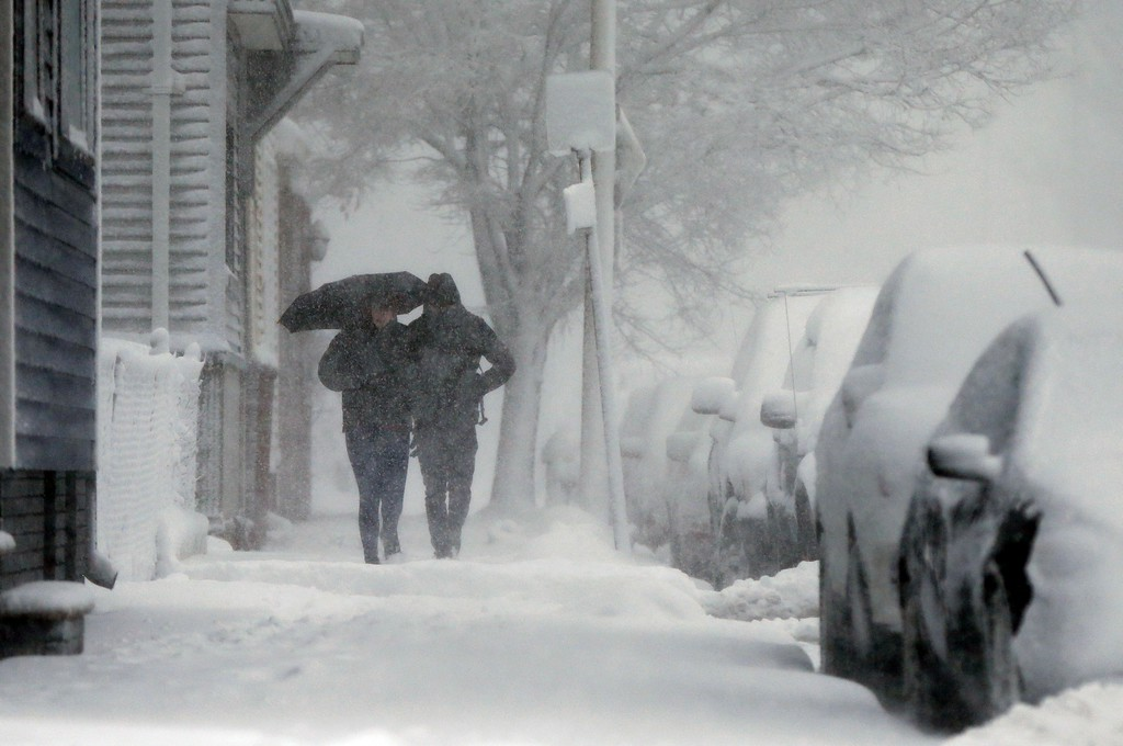 . A couple walks on Marginal Street in Boston, Tuesday, March 13, 2018. The National Weather Service issued a blizzard warning for much of the coast of Maine, New Hampshire, and Massachusetts.  (AP Photo/Michael Dwyer)