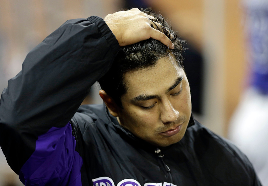 . Colorado Rockies starting pitcher Jorge De La Rosa puts his hand on his head in the dugout after the Miami Marlins scored three runs in the fifth inning after he was relieved during an opening day baseball game, Monday, March 31, 2014, in Miami. (AP Photo/Lynne Sladky)