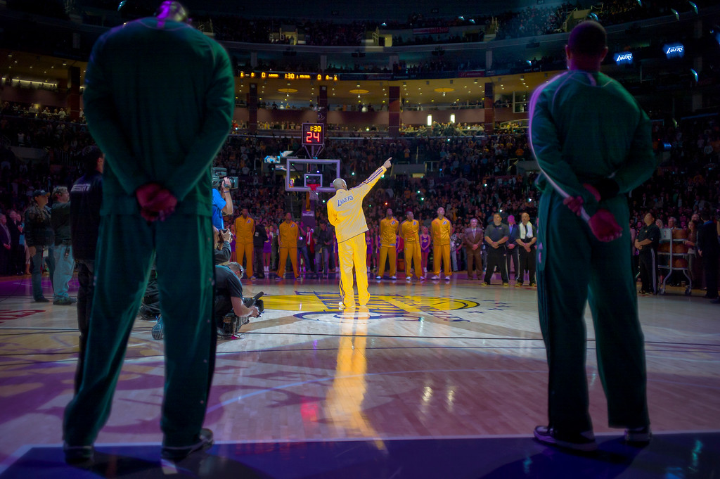 . Lakers Kobe Bryant points to Jerry Buss\'s seat as Boston Celtics players look on before the start of the Lakers game Wednesday.  Jerry Buss passed away last week.  Photo by David Crane/Staff Photographer
