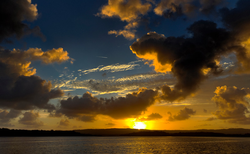 Golden colored coastal sunrise seascape cloudscape.