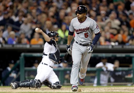 . Minnesota Twins\' Eduardo Escobar (5) looks to the dugout after walking against Detroit Tigers relief pitcher Joe Nathan with the bases loaded to score Sam Fuld in ninth inning of a baseball game in Detroit, Friday, June 13, 2014. (AP Photo/Paul Sancya)