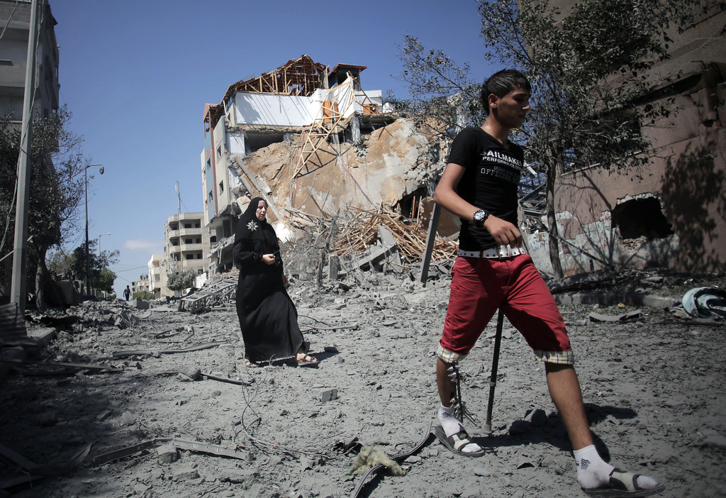 . Palestinians walk past the Hamas movement\'s Al-Aqsa satellite TV station which was hit by an Israeli strike in Gaza City, Thursday, July 31, 2014. (AP Photo/Khalil Hamra)