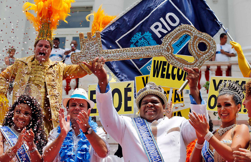 . Rio de Janeiro\'s Mayor Eduardo Paes (2nd L) claps his hands after he handed over the ceremonial key to the city to the Rei Momo, or Carnival King, Milton Junior (2nd R) at Cidade Palace in Rio de Janeiro February 8, 2013. The event officially kicks off the 2013 carnival week in Rio.  REUTERS/Sergio Moraes