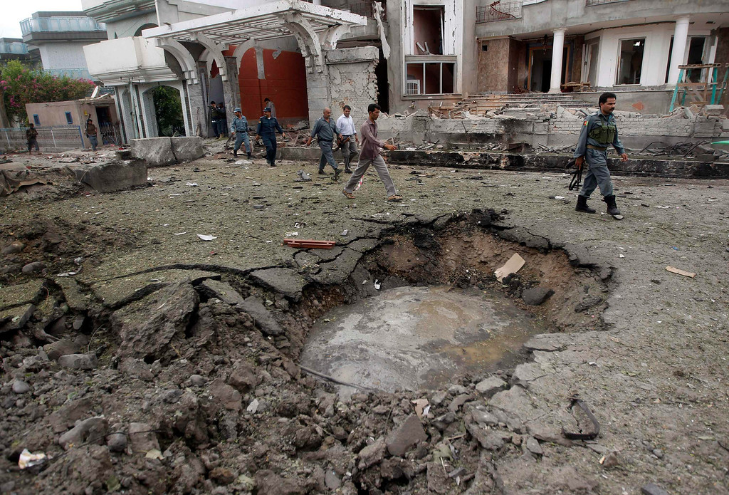 . Afghan policemen walk near a crater at the site of a suicide attack at the Indian consulate in Jalalabad province August 3, 2013. A suicide bomber attacked the Indian consulate in the eastern Afghan capital of Jalalabad on Saturday, Indian officials and local police said, killing six people and wounding 22. REUTERS/Parwiz