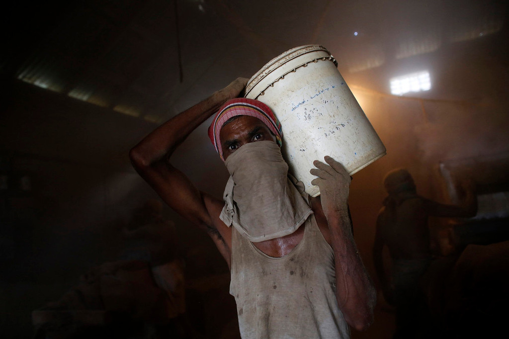 """. A worker carries a bucket while he works in a small bidi (cigarette) factory at Haragach in Rangpur district, Bangladesh July 13, 2013. According to a 2012 study by US-based NGO, Campaign for Tobacco-Free Kids, over 45,000 people in Bangladesh are employed in manufacturing inexpensive cigarettes known as bidis and this number includes \""""many women and children working in household based establishments where they make low wages and live in poverty.\"""" A 2011 research paper about bidi workers in Bangladesh, published in the journal Tobacco Control, says that working conditions can involve poor ventilation and exposure to tobacco dust, which can cause a range of health problems including respiratory and skin diseases. International attention has been focused on workers\' safety in Bangladesh since the disaster at Rana Plaza, a garment factory complex which collapsed in April, killing 1,132 workers.   REUTERS/Andrew Biraj"""