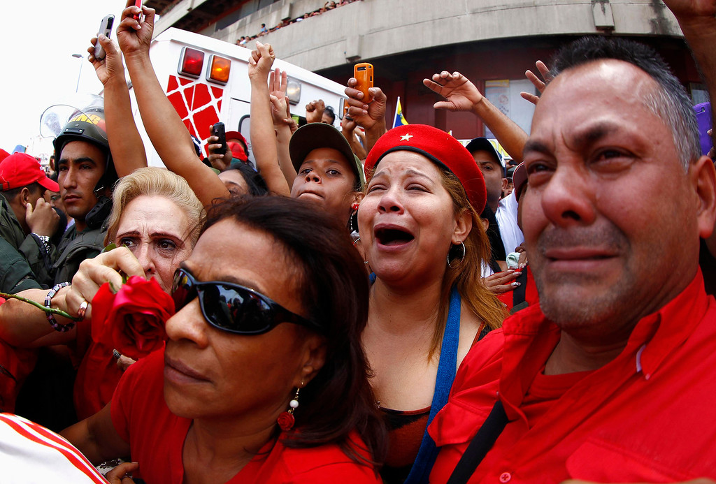 . Supporters of deceased Venezuelan leader Hugo Chavez react as his coffin is driven through the streets of Caracas, March 6, 2013. Venezuela\'s late President Chavez died on Tuesday of cancer, and authorities have not yet said where he will be buried after his state funeral on Friday. REUTERS/Carlos Garcia Rawlins