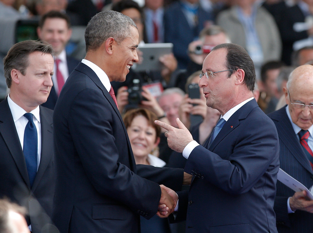 . French President Francois Hollande, right, speaks with U.S. President Barack Obama as British Prime Minister David Cameron, left, looks on during the D-Day commemoration at the Ouistreham beach, western France, Friday, June 6, 2014.  (AP Photo/Christophe Ena, Pool)