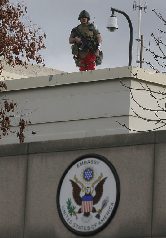 . A U.S. soldier stands guard at the entrance of the U.S. embassy in Ankara February 1, 2013. A suicide bomber killed a Turkish security guard at the U.S. embassy in Ankara on Friday, blowing the door off a side entrance and sending smoke and debris flying into the street. Ankara Governor Alaaddin Yuksel said the attacker was inside U.S. property when the explosives were detonated. The blast sent masonry spewing out of the wall of the side entrance, but there did not appear to be any more significant structural damage. REUTERS/Stringer