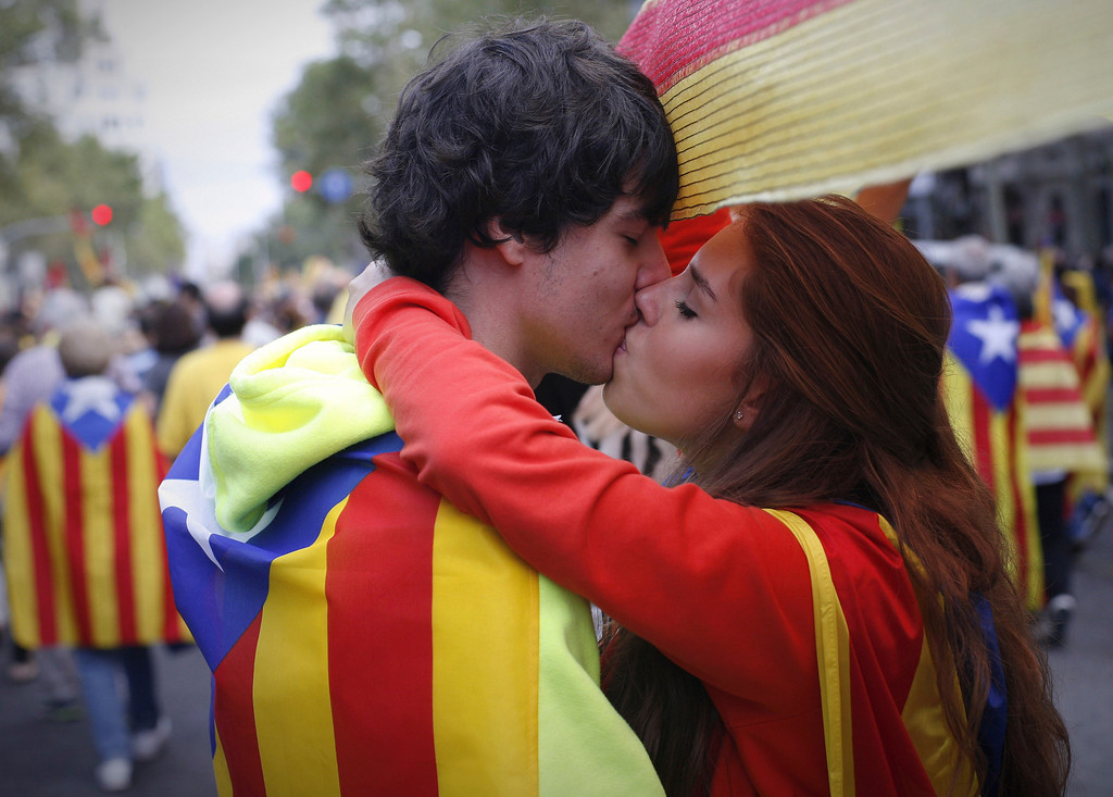 . A couple draped with Catalonian national flags kiss in Barcelona, Spain Wednesday Sept. 11, 2013. Several hundred thousand people demanding an independent Catalonia have joined hands in an attempt to form a 400-kilometer (250-mile) human chain across the northeastern region of Spain. The demonstration Wednesday aimed to illustrate local support for political efforts to break away from Spain. Organizers estimated about 400,000 people took part in the human chain. Catalonia claims a deep cultural difference based on its language, which is spoken side-by-side with Spanish in the wealthy region. (AP Photo/Paco Serinelli)