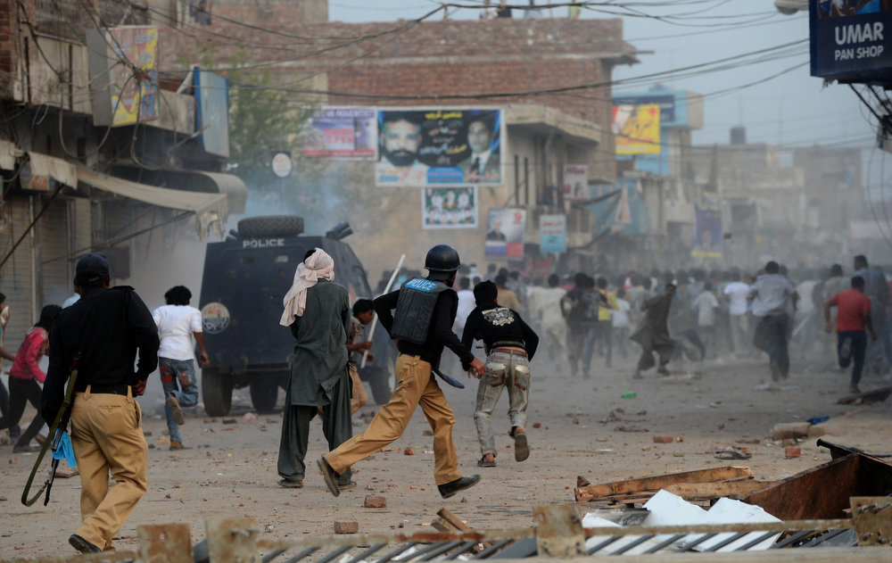 . Pakistani policemen chase Christian demonstrators during a protest against the attack on the homes of members of the Christian community by Muslim demonstrators in Lahore on March 10, 2013. Christians demonstrated around Pakistan on March 10 to protest after a Muslim mob torched more than 100 Christian homes following allegations of blasphemy. More than 3,000 Muslims rampaged through Joseph Colony, a Christian area of the eastern city of Lahore, on March 9 after allegations that a Christian had made derogatory remarks about the Prophet Mohammed three days earlier. Arif Ali/AFP/Getty Images